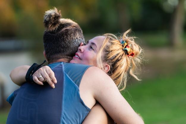 公園で抱きしめるスポーティーな男女