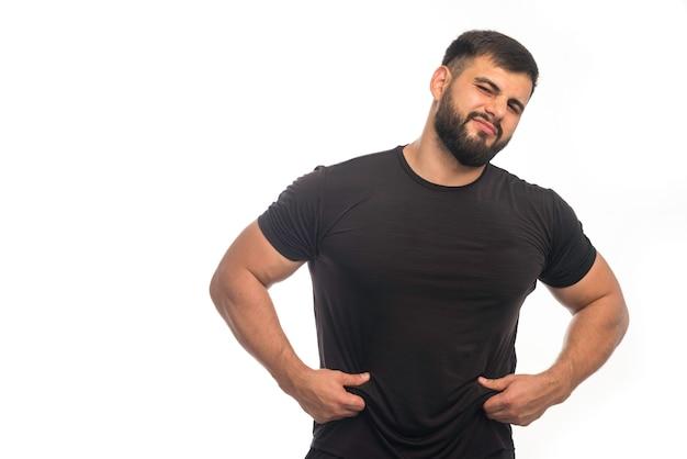 L'uomo sportivo in camicia nera ha un peso eccessivo.