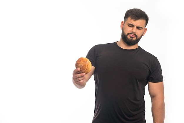 Sportive man in black shirt holding a doughnut and refusing
