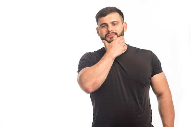Sportive man in black shirt putting his hand to his cheek.