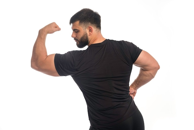 Sportive man in black shirt showing his biceps muscle.