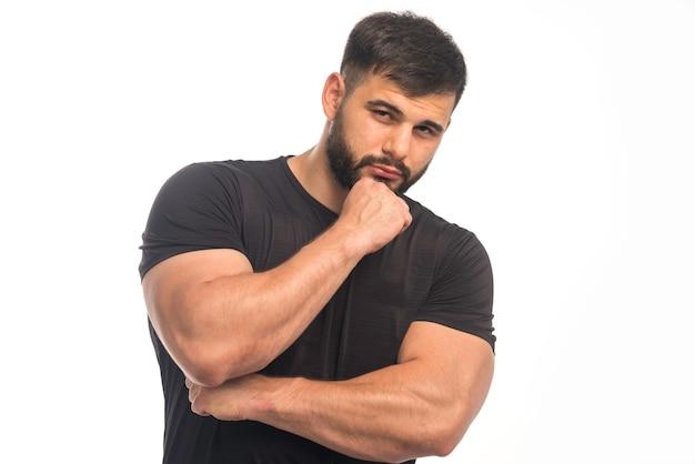 Uomo sportivo in camicia nera che mostra i pugni e prende posizione di pensiero.
