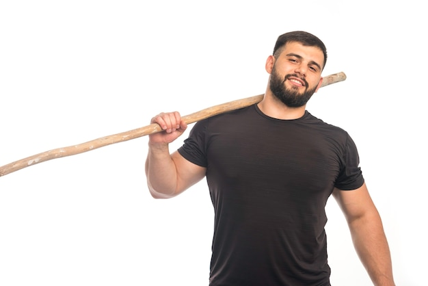 木製のカンフースティックを保持しているスポーツ男。