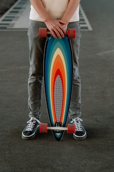 Sportive man holding bright colorful longboard caucasian male hipster skateboarder with skateboard