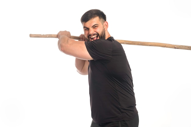 Sportive man holding a wooden kung fu stick