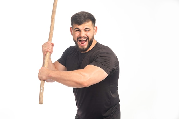 Sportive man holding a wooden kung fu stick.