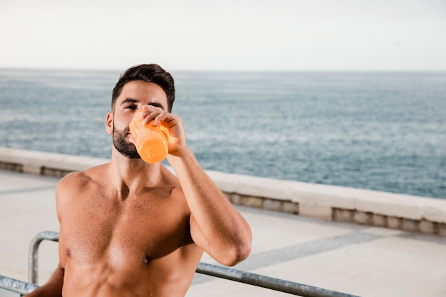 Sportive man hydration process after exercising