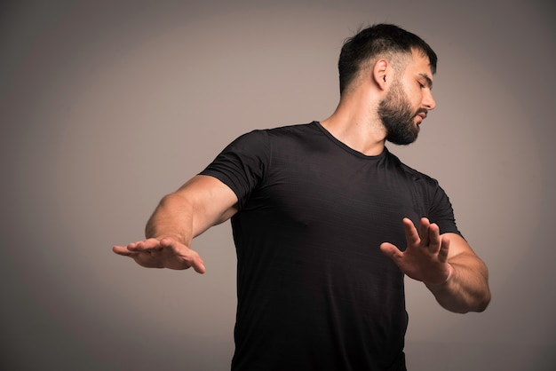 黒のシャツを着たスポーティーな男は身を守り、戦いを避けます。