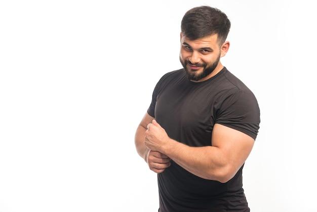 Спортивный мужчина в черной рубашке демонстрирует мышцы рук.
