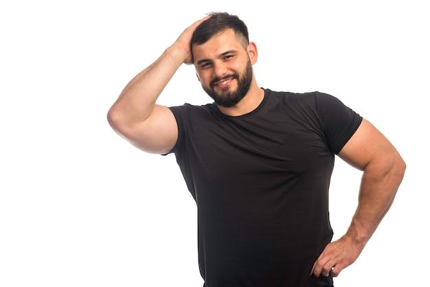 Спортивный мужчина в черной рубашке чувствует себя сильным