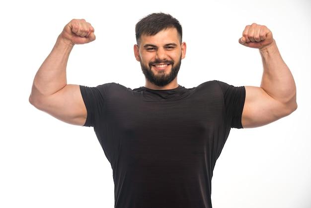 Спортивный мужчина в черной рубашке чувствует себя сильным.