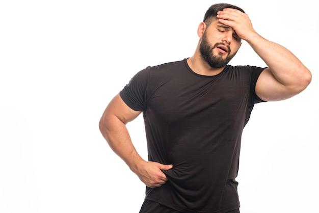 黒のシャツを着たスポーティーな男は頭痛がします。