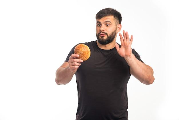 Спортивный мужчина в черной рубашке держит пончик и отказывается есть.