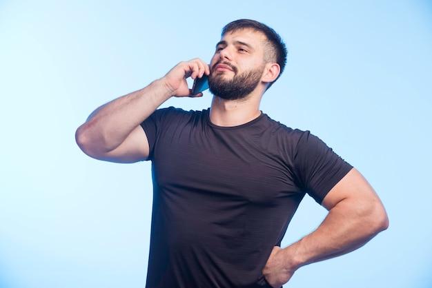 黒いシャツを着た陽気な男が電話と会談を保持しています。
