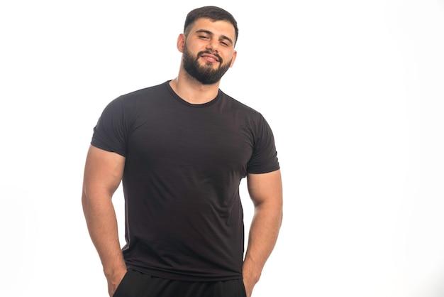검은 셔츠 포즈에 낚시를 좋아하는 남자.