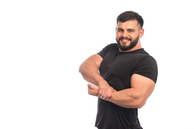 彼の腕の筋肉に彼の手を置く黒いシャツを着たスポーティーな男。