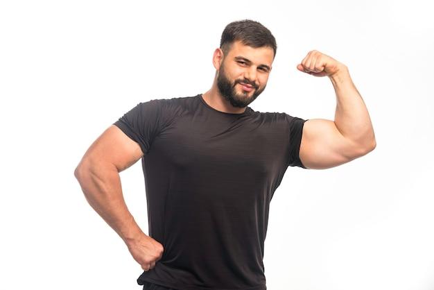 Спортивный мужчина в черной рубашке показывает мышцы руки.