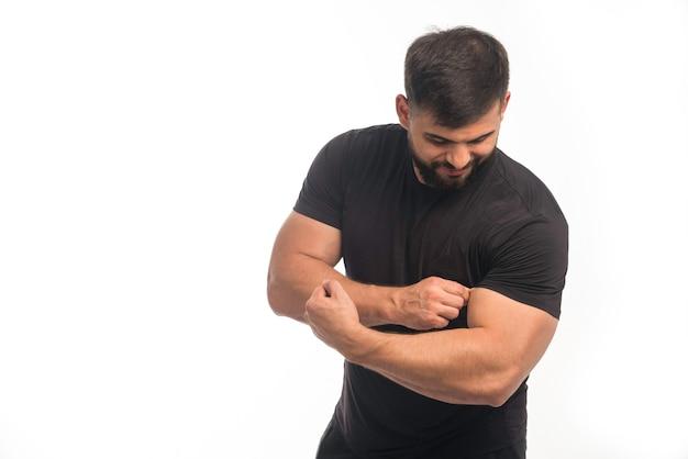 彼の上腕二頭筋を示す黒いシャツで陽気な男
