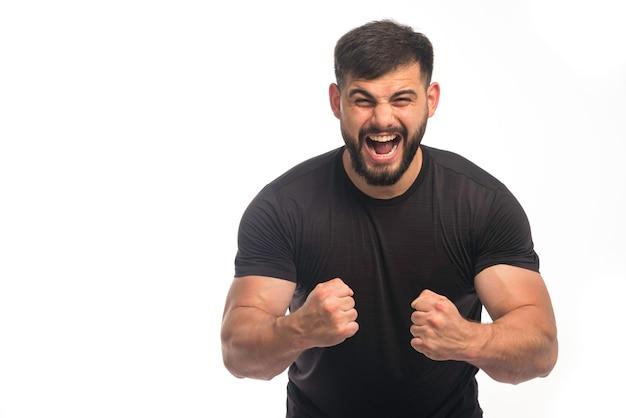 上腕二頭筋を示す黒いシャツを着たスポーティーな男。
