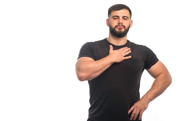 Спортивный мужчина в черной рубашке показывает свое стройное тело.