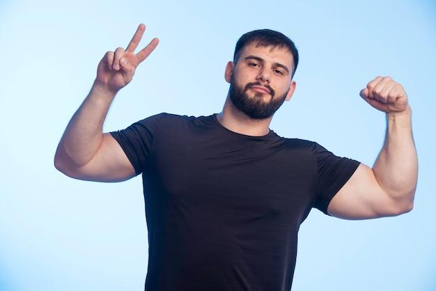 Спортивный мужчина в черной рубашке показывает свои мышцы и делает знак мира.