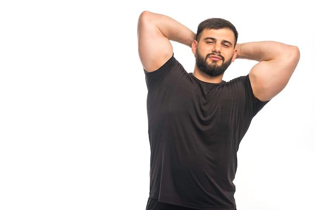 Спортивный мужчина в черной рубашке, показывая его трицепс