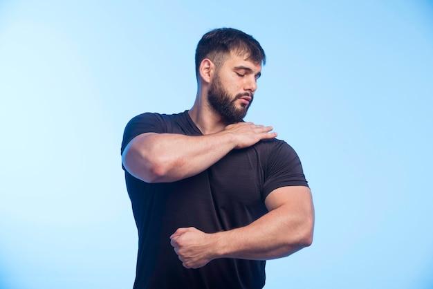 Спортивный мужчина в черной рубашке показывает свои мышцы
