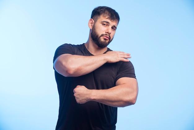 Спортивный мужчина в черной рубашке показывает свои мышцы.