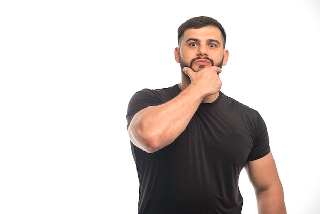 Спортивный мужчина в черной рубашке, касаясь его бороды.
