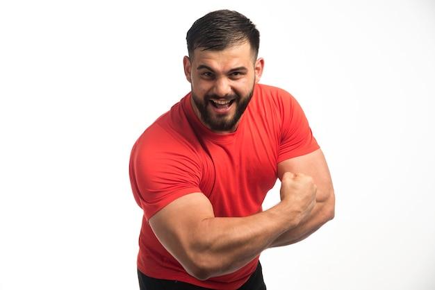 Спортивный мужчина в красной рубашке демонстрирует мышцы рук