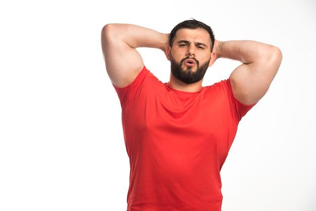 彼の筋肉を示し、彼の頭に手を置く赤いシャツを着たスポーティーな男。