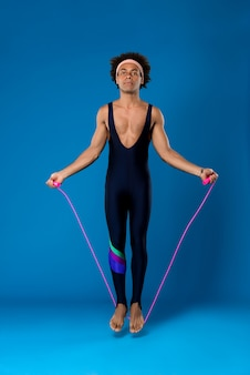 Sportive man jumping with skipping rope