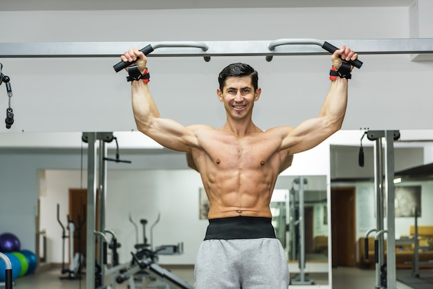Sportive man making exercises on crossbar in gym