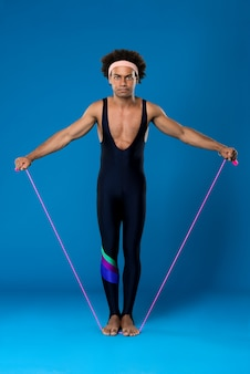 Sportive man posing with skipping rope