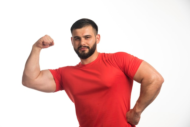 Sportive man in red shirt demonstrating his arm muscles and looks confident