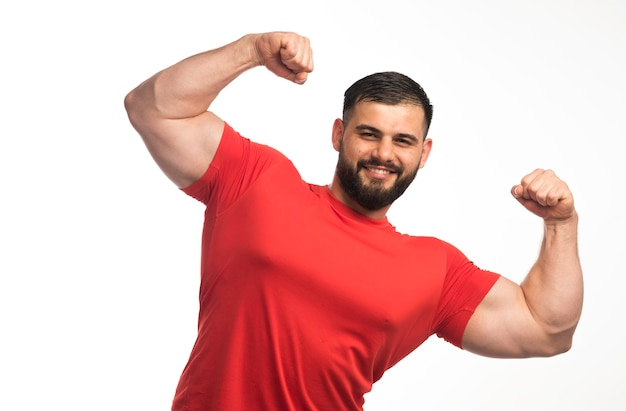Sportive man in red shirt demonstrating his arm muscles and looks confident.
