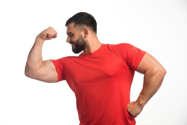 Uomo sportivo in camicia rossa che dimostra i suoi muscoli del braccio e sembra fiducioso.