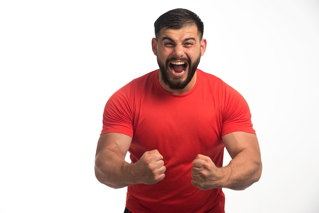 Uomo sportivo in camicia rossa, dimostrando i muscoli delle braccia e urlando