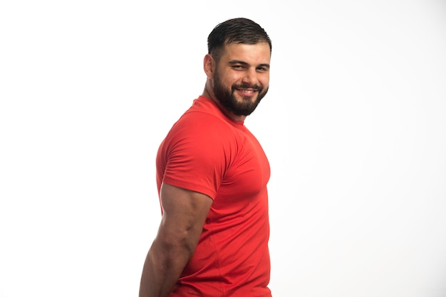 Sportive man in red shirt demonstrating his arm muscles and smiling