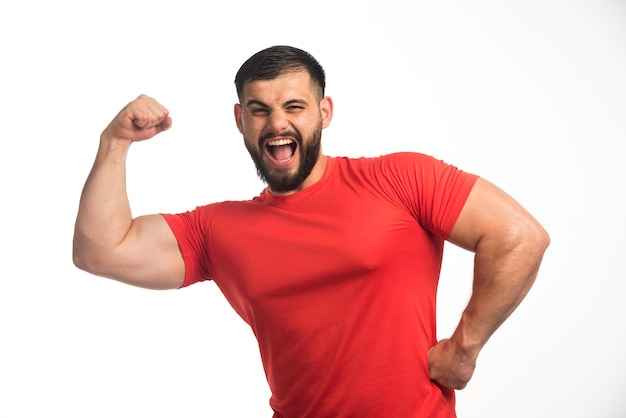 Sportive man in red shirt demonstrating his arm muscles and yelling.