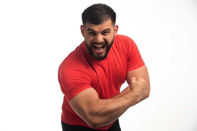 Sportive man in red shirt demonstrating his arm muscles .