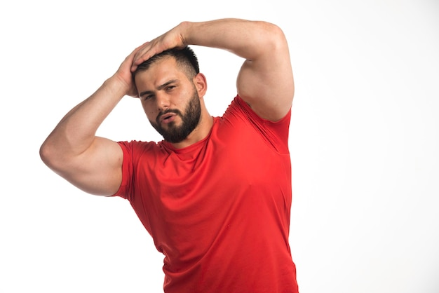 Sportive man in red shirt demonstrating his muscles and put hands to his head.