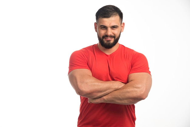Sportive man in red showing his muscles.