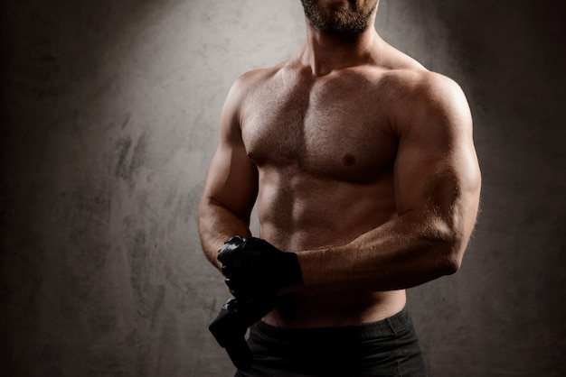 Sportive man's body over dark wall.