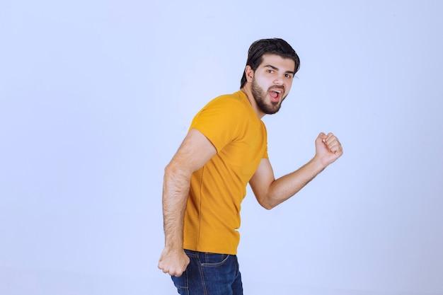 Uomo sportivo che mostra i pugni e si sente potente