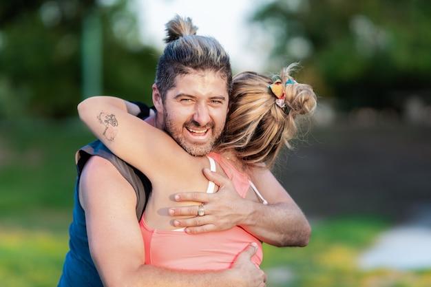 公園で女性を抱きしめながら笑うスポーティーな男