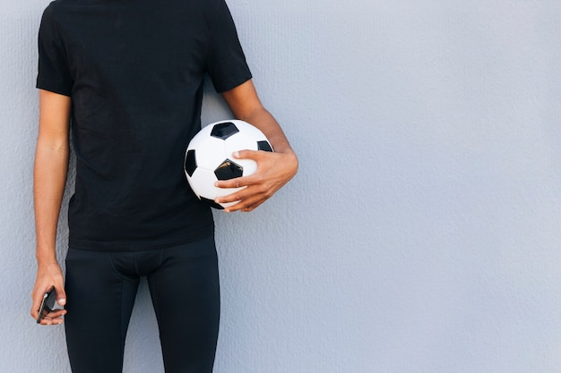 Sportive man standing with football and phone