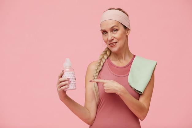 水のボトルを保持している陽気なmatre女性