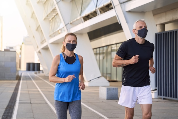 Спортивная зрелая пара в защитных масках вместе бегает трусцой в городской среде