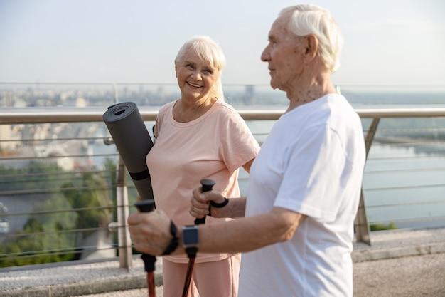 Спортивная зрелая женщина и мужчина стоят на мосту в современном городе при свете заката